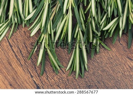 Rosemary bound on a wooden board - stock photo