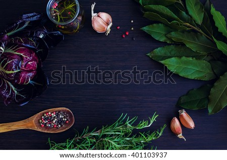 Rosemary, garlic, chicory, Bay leaf, olive oil with spices, wooden spoon with pepper on dark background. Background layout with free text space. Copy space. Top view. Food flat lay. - stock photo