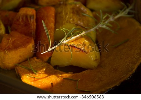 Rosemary on baked rustic potato, pumpkin and vegetables straight from the oven. - stock photo