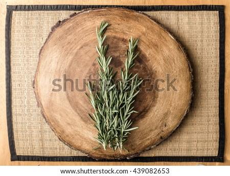 rosemary on circular wooden chopping board - stock photo