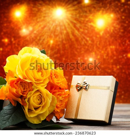 roses and a present in front of a firework scene - stock photo