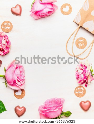 Roses , chocolate heart and shopping bag with love message cards on white wooden background, top view, frame.  - stock photo
