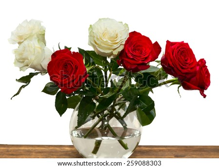roses in a clear vase on a wooden table on a white background - stock photo