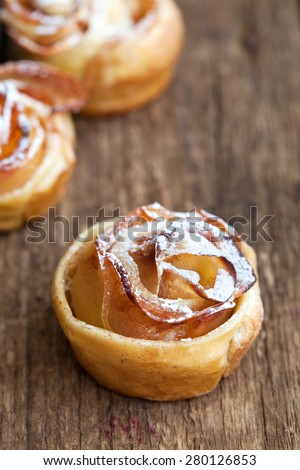 Roses made from puff pastry with petals of apple and cinnamon on a wooden table, selective focus - stock photo