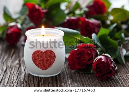 roses with candle on wooden background  - stock photo