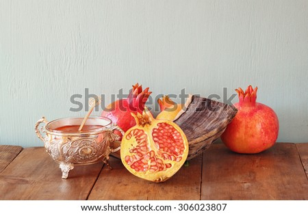 rosh hashanah (jewesh holiday) concept - shofar, honey, apple and pomegranate over wooden table. traditional holiday symbols.  - stock photo