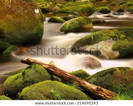 Rot trunk blocked on stones. Stream bank above bright blurred waves. Big mossy boulders in clear water of mountain river. - stock photo