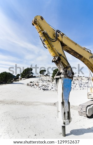 rotary hammer placed on an excavator in a granite quarry - stock photo