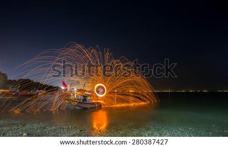 Rotate show fire near beach in thailand - stock photo
