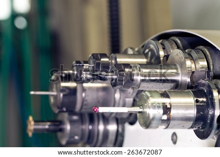 Rotating head with drilling machine bits and tools in a high precision mechanics plant at CNC lathe in workshop  - stock photo