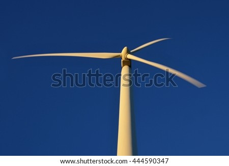 Rotating light gray propeller wind power station use the renewable wind energy. Shot at sunset with dark blue sky. - stock photo
