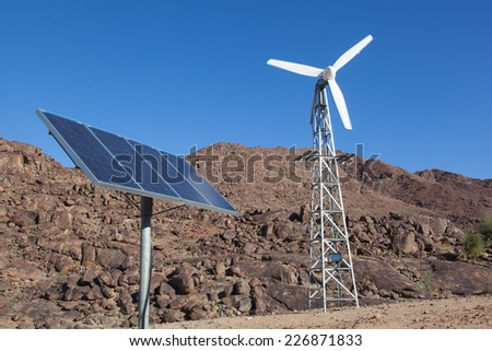 rotating small wind generator and solar panel on masts in a desert with the rocky mountains and a blue sky - stock photo