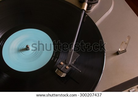 Rotating vinyl record with a blue mark on the turntable view from the top selective focus - stock photo
