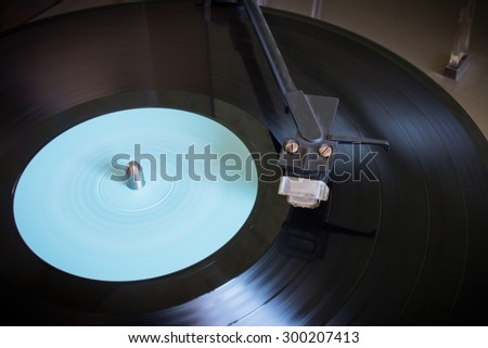 Rotating vinyl record with blue label on a turntable close-up selective focus - stock photo