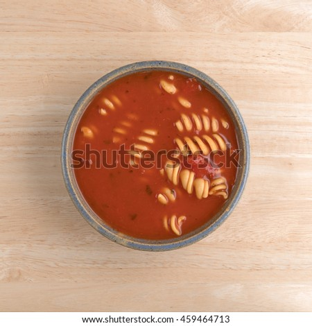 Rotini tomato soup in an old stoneware bowl on a wood table top view. - stock photo