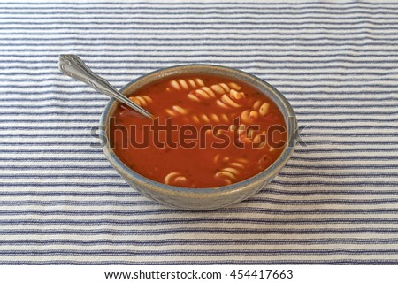 Rotini tomato soup in an old stoneware bowl with a spoon inserted into the food on a blue striped tablecloth. - stock photo