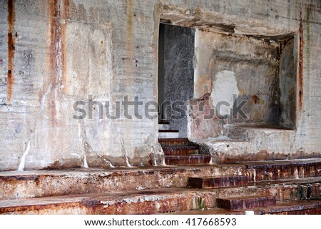 Rotten dirty and decayed concrete wall and stair with rust staining from exposed steel details like the stair tread capping - stock photo