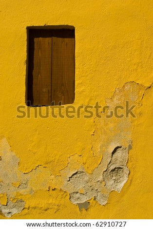 Rotten yellow wall with blinded window, taken in Greece. - stock photo