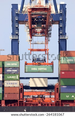 ROTTERDAM - AUG 1, 2014: Crane operator placing a container in a cargo ship the Port of Rotterdam. The port is the Europ's largest and facilitate the needs of a hinterland with 40,000,000 consumers. - stock photo