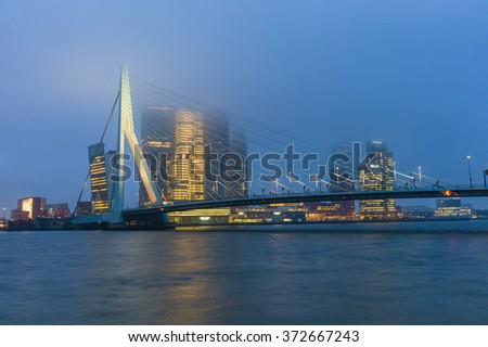"ROTTERDAM, FEBRUARY 5, 2016 AT 8:03 AM CET. View on the Erasmus bridge over the river ""Nieuwe Maas"" with a backdrop of the skyscrapers on the Wilhelmina Pier on a foggy morning. - stock photo"