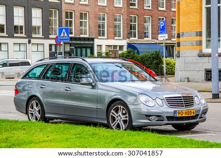 ROTTERDAM, NETHERLANDS - AUGUST 9, 2014: Motor car Mercedes-Benz S211 E-class at the city street. - stock photo