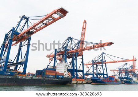 ROTTERDAM, NETHERLANDS - JUNE 28, 2015: Large harbor cranes loading container ships. Rotterdam is the largest harbor in Europe. - stock photo