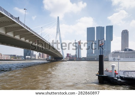 ROTTERDAM, NETHERLANDS, MAY 10 - Erasmus bridge in Rotterdam and business buildings in the background on 10 May 2015, - stock photo