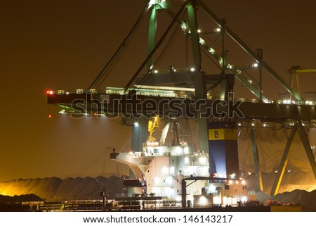 ROTTERDAM - NOVEMBER 13: A bulkcarrier unloading cargo on November 13, 2011 in Rotterdam, Holland. The port of Rotterdam plays a main role in the international transfer and transit of ore deposits  - stock photo