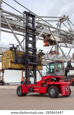 ROTTERDAM - SEP 8, 2013: Mobile container handler in the Port of Rotterdam, The Netherlands. The port is Europo's largest and facilitate the needs of a hinterland with 40,000,000 consumers. - stock photo