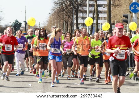 ROTTERDAM, THE NETHERLANDS ? APRIL 12, 2015: Runners on the streets enjoying their run in the 35th NN Rotterdam Marathon held in the city center. The marathon is well known for its fast times. - stock photo