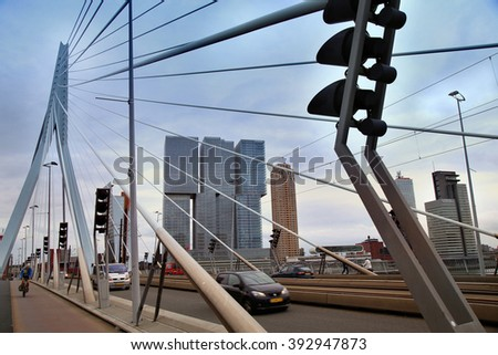 ROTTERDAM, THE NETHERLANDS - 18 AUGUST: Cars traffic driving and bicyclists crossing on the Erasmus bridge (Erasmusbrug) in Rotterdam, Netherlands on August 18,2015. - stock photo