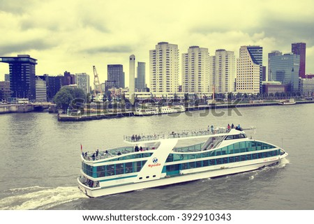 ROTTERDAM, THE NETHERLANDS - 18 AUGUST: View from Erasmus bridge on skyline of Rotterdam with a cruise boat, river Maas in Rotterdam, Netherlands on August 18,2015.