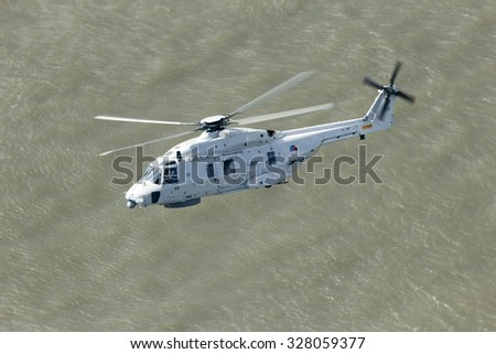 ROTTERDAM, THE NETHERLANDS - SEP 5, 2015: Royal Netherlands Navy NH90 helicopter flying over the Meuse river. - stock photo