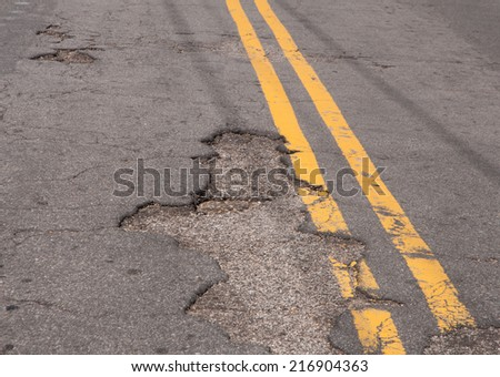 Rough patched roads and potholes in pavement of a city street - stock photo