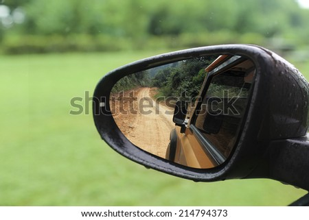 rough road in rear mirror show adventure - stock photo