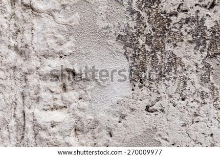 Rough texture of an ancient block of stone part of an external wall. Cavernous rock structure with brittle surface. Pale gray and beige colors with dark streaks. Close up shot outdoors on a tripod. - stock photo