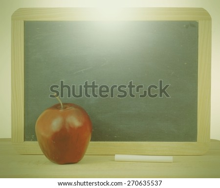 Rough textured blackboard with wooden frame. A red apple and a stick of white chalk sit in front. The blank black slate has a used or worn appearance with copy space. Color and light filters applied - stock photo