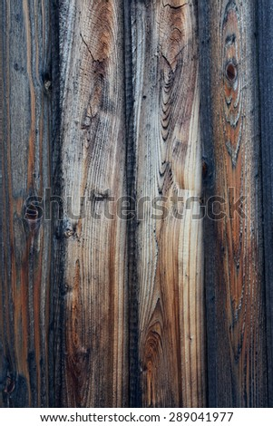 Rough textured wood plank fence. Wood panels show various colors and stages of weathering, from darker, medium browns to light colored sections. Vertical background image. - stock photo