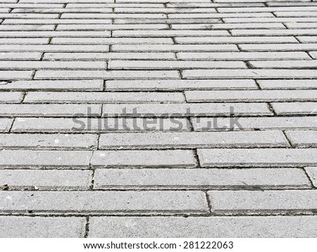 Rough, tiled floor outside a commercial building - stock photo