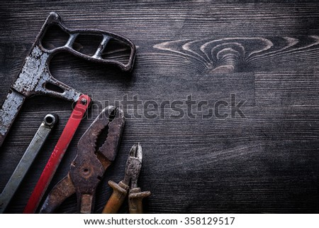 Rough vintage handsaw wire-cutter pliers on wooden board construction concept. - stock photo