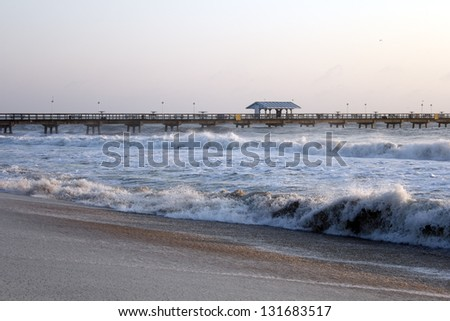 Rough waves pound the coast of Lauderdale by the Sea, Florida a few days after Hurricane Sandy passed by the area closing Anglers Pier for a while. - stock photo