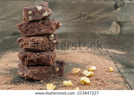 Roughly cut chunks of homemade chocolate on vintage wooden background. Traditional western confectionery with nuts and cocoa - stock photo