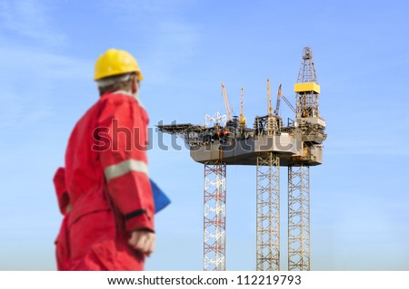Roughneck (out of focus) looking at a huge oil rig being constructed. - stock photo