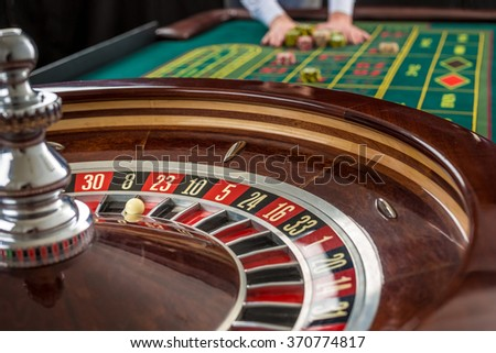 Roulette and piles of gambling chips on a green table.  - stock photo