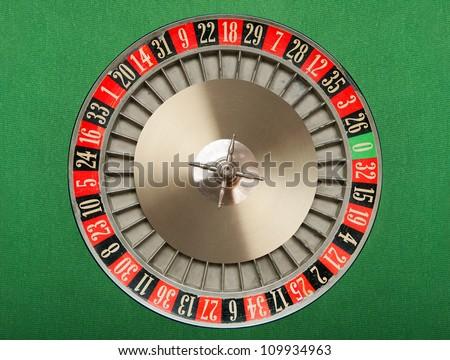 Roulette wheel on green felt - stock photo