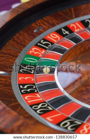 Roulette wheel stopping and ball landing on black 26 - stock photo