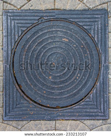 Round and quadrant  steel sewer manhole on pavement  - stock photo