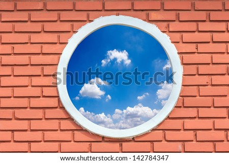 round and vintage window against blue sky on a brick wall building - stock photo