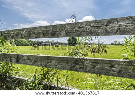 Round bales of hay are seen through the rails of an old fence surrounding a farm field in rural Ontario Canada. A barn is in the distance. - stock photo