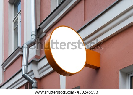 Round blank signboard on the wall - stock photo
